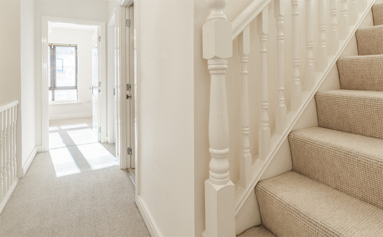 Beautiful beige carpet in the upstairs hallway and stairs leading to the third level